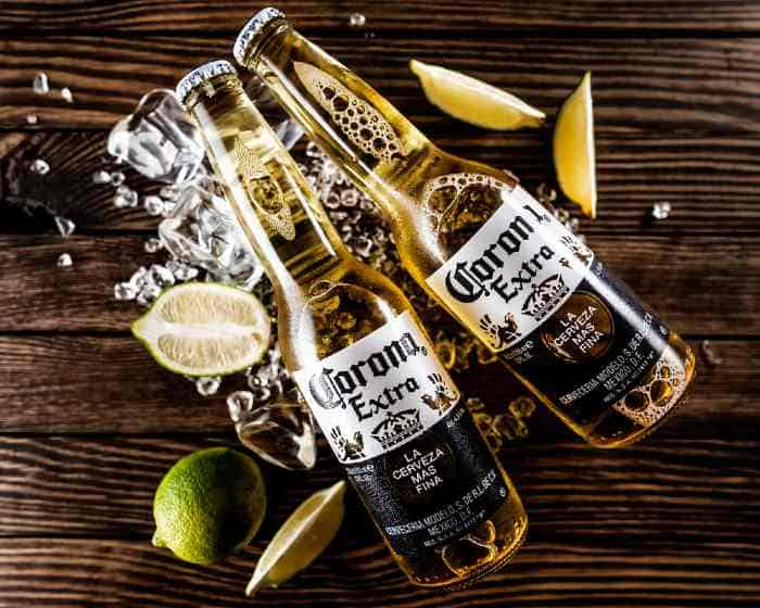 Two bottles of cold Corona Extra on wooden table